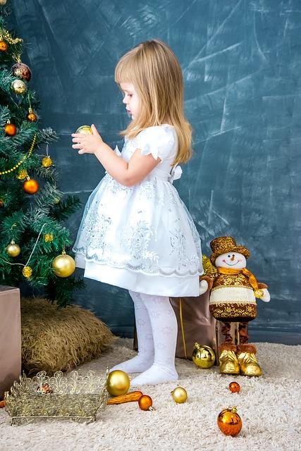Дети наряжают новогоднюю ёлку игрушками