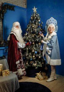Дед Мороз и Снегурочка наряжают новогоднюю елку игрушками
